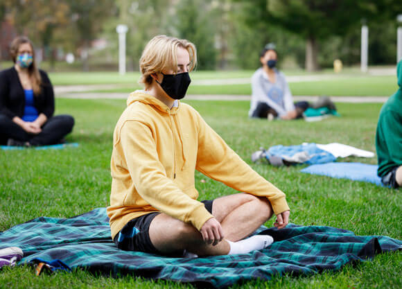 Students in face masks do meditation on the quad