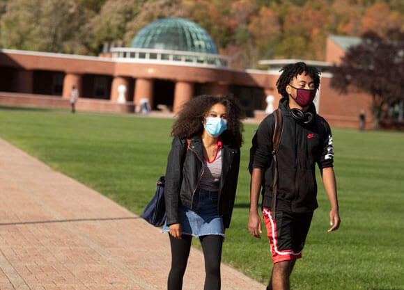 Two students in face coverings walk across the quad
