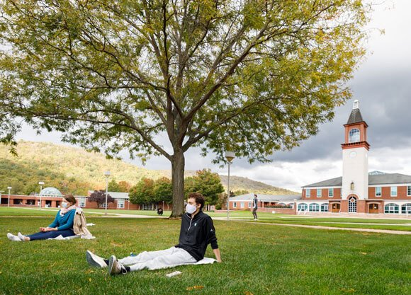 Two students in face masks participate in a meditation on the quad