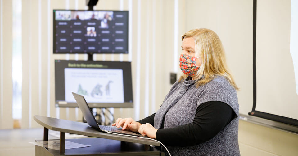 Faculty member teaches class wearing a face covering and using a Zoom cart