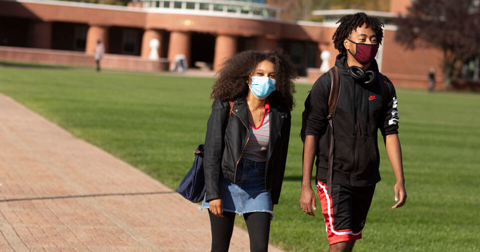 Students wearing face covering walk across the quad