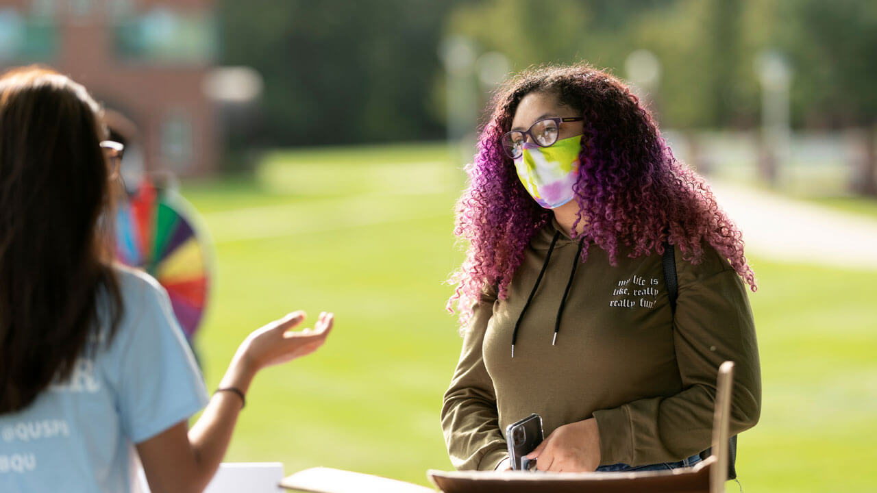 Students wearing masks interact during involvement fair