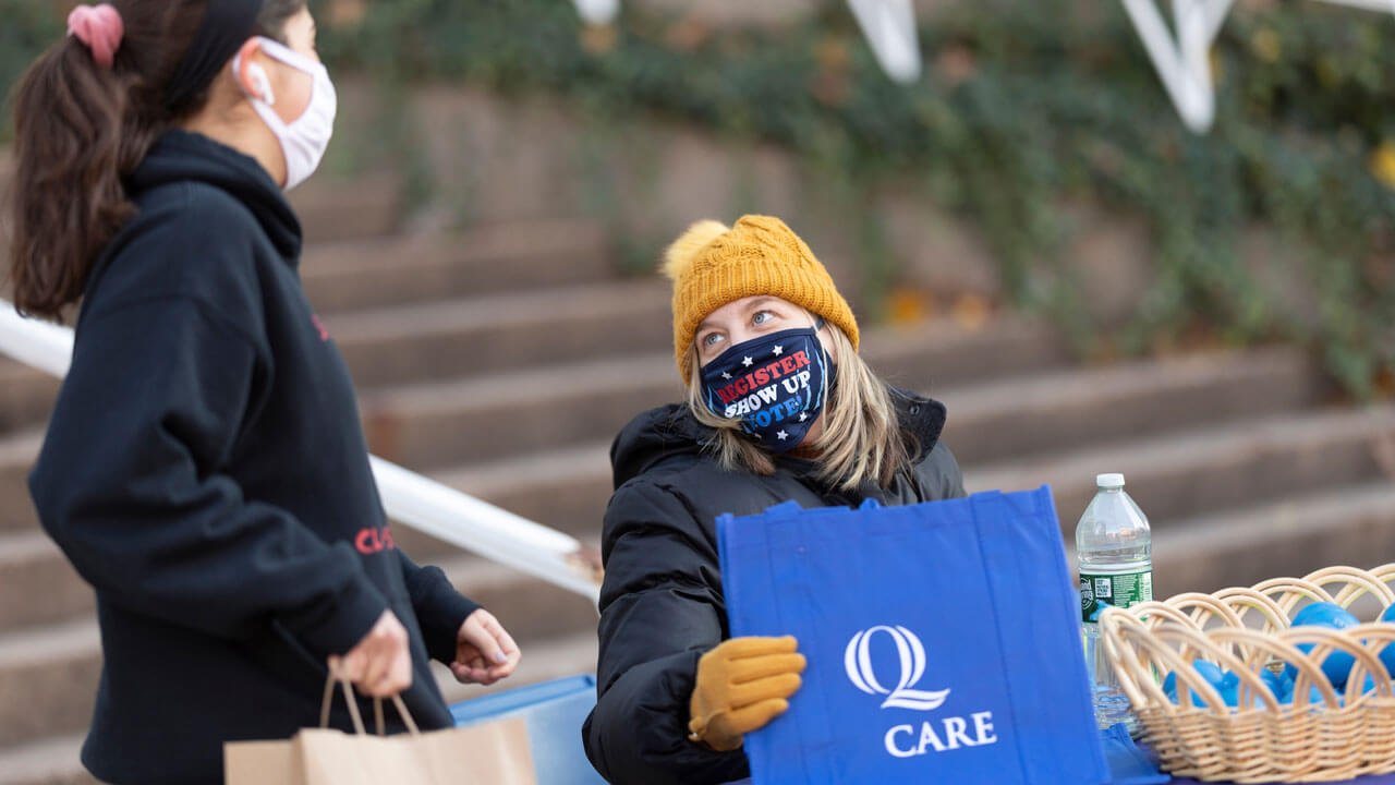 Students in masks talk outside socially distanced