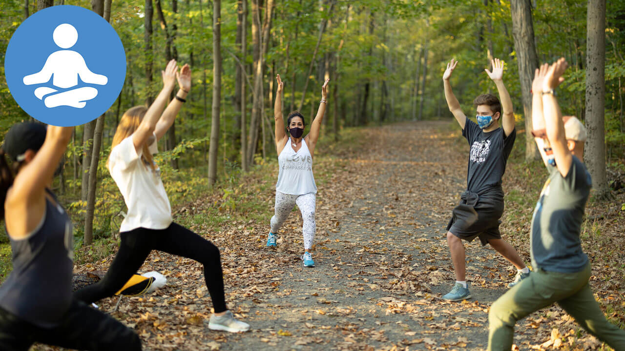 Students and staff strike a yoga pose in the woods