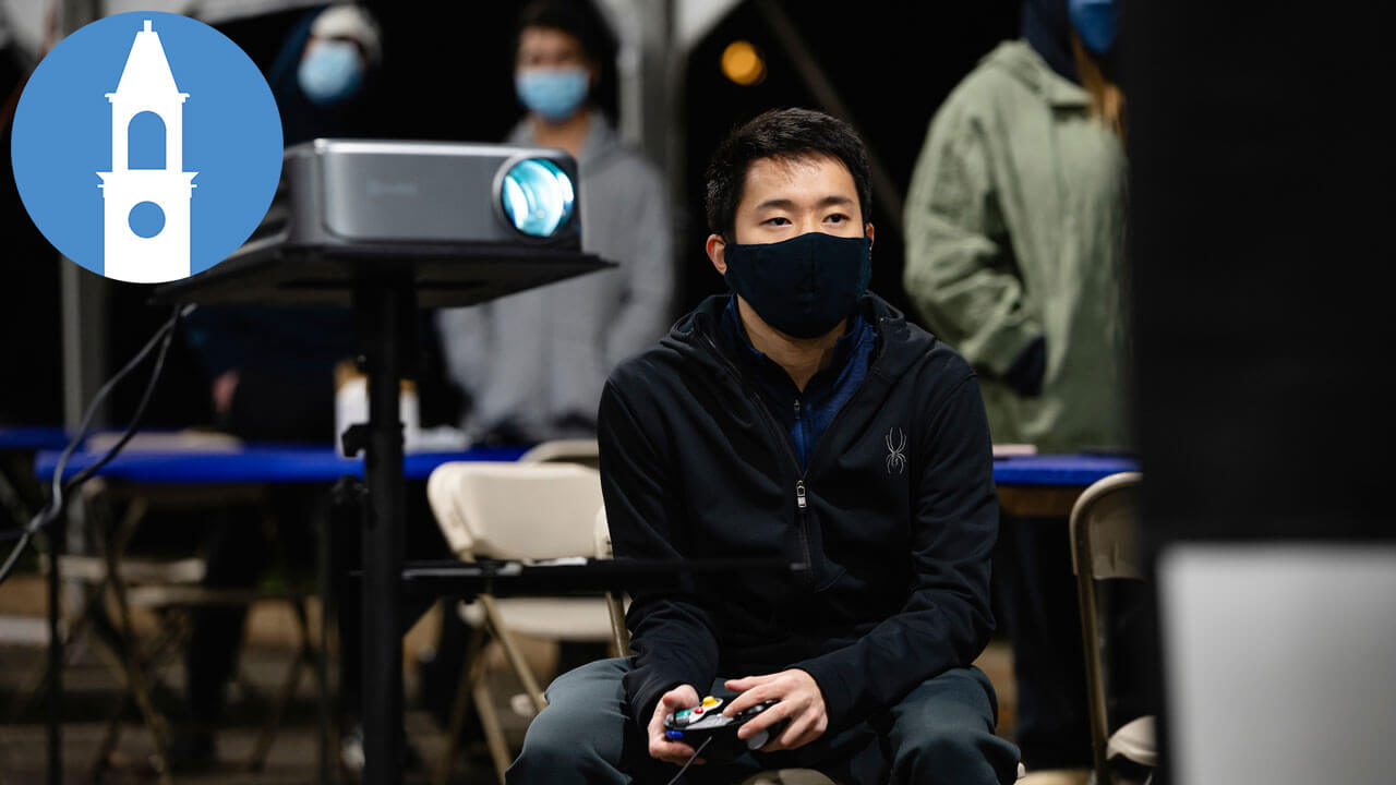 A student wearing a face covering plays Super Smash Bros