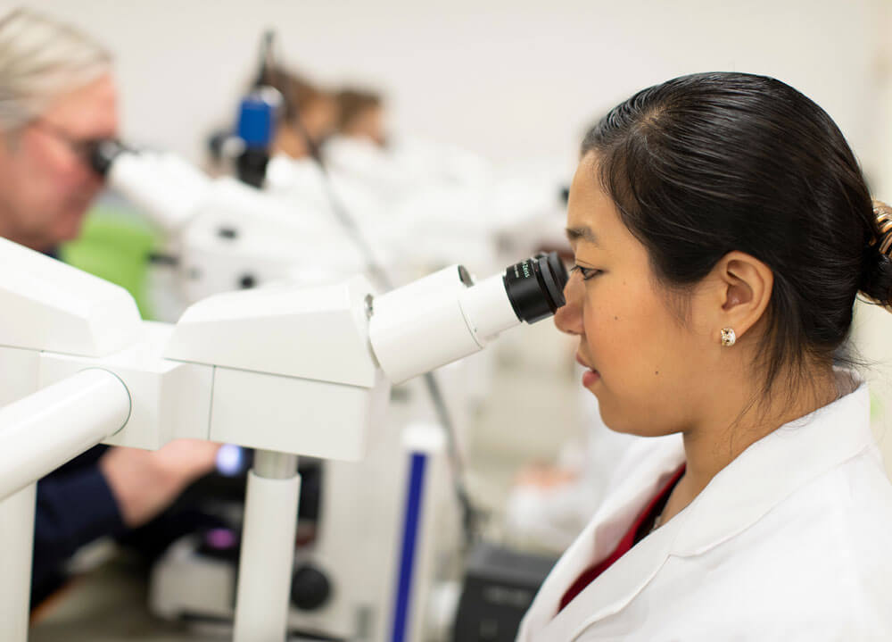 A student wearing a white coat looking into a microscope.