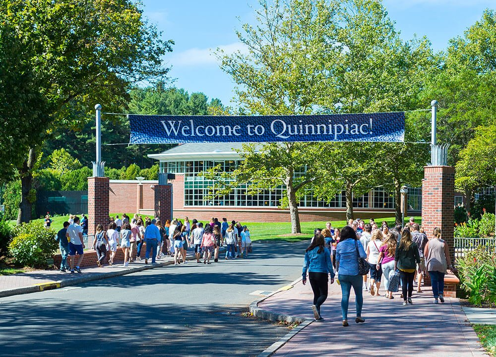 "A group of students and their parents walk down Bobcat Way under a ""Welcome to Quinnipiac"" banner"