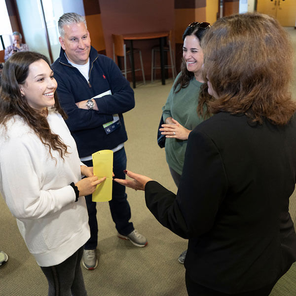 A student and her two parents greet a faculty member on North Haven Campus