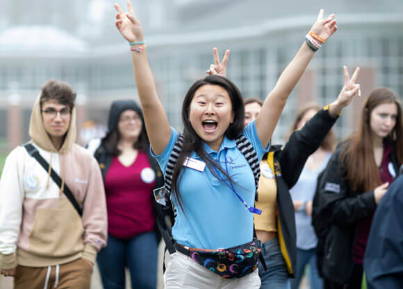 An orientation leader cheers as she walks with new students