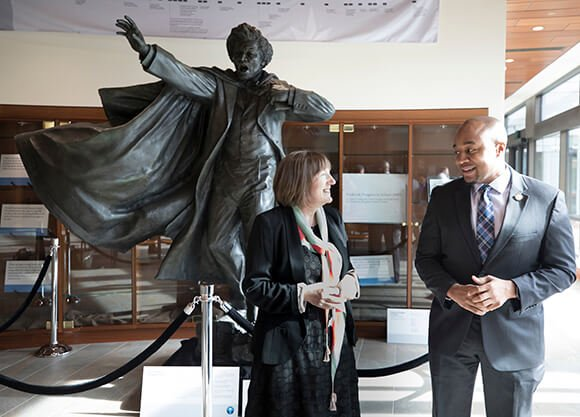 Christine Kinealy and Don Sawyer gesture in front of a statue of Frederick Douglass