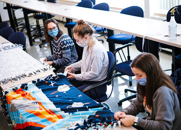 Students making tie blankets in masks