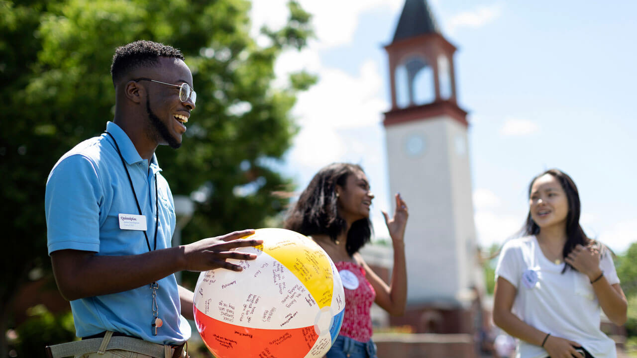 Orientation leader holding a beach ball on the quad surrounding by students