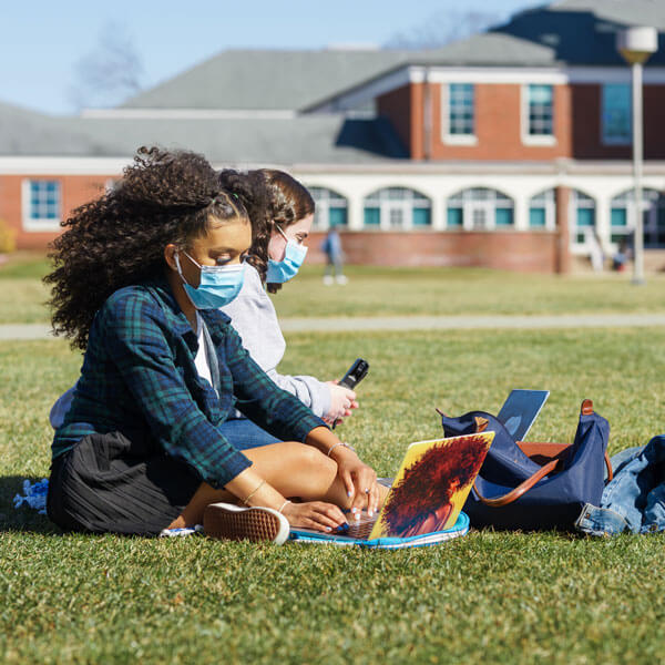 Two students sit on the quad doing work on their laptops