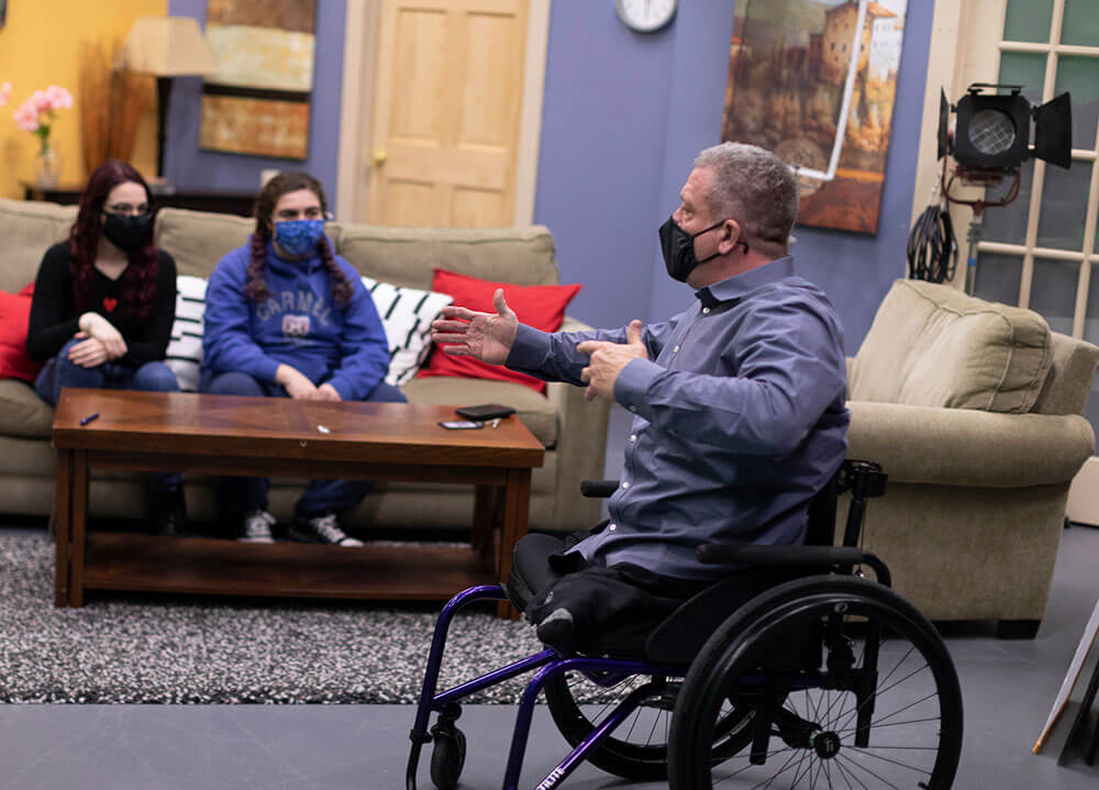 Instructor Dave Stevens sits in a wheelchair and speaks with communications students in the broadcast studio on campus