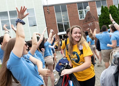 An admitted student enters campus for orientation among a crowd of cheering students
