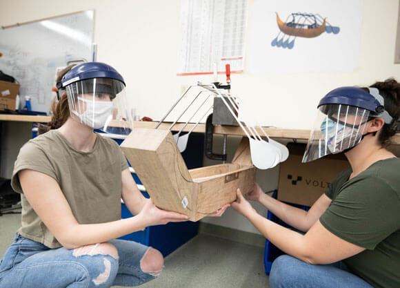 School of Engineering students Madeline LePage (left) and Gabriella Ambery work on their senior projects while wearing face shields and masks and holding a block of wood.