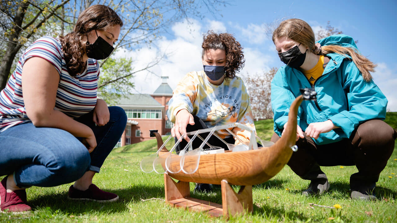 Three students sit in the grass on campus with a wooden row boat in the center.