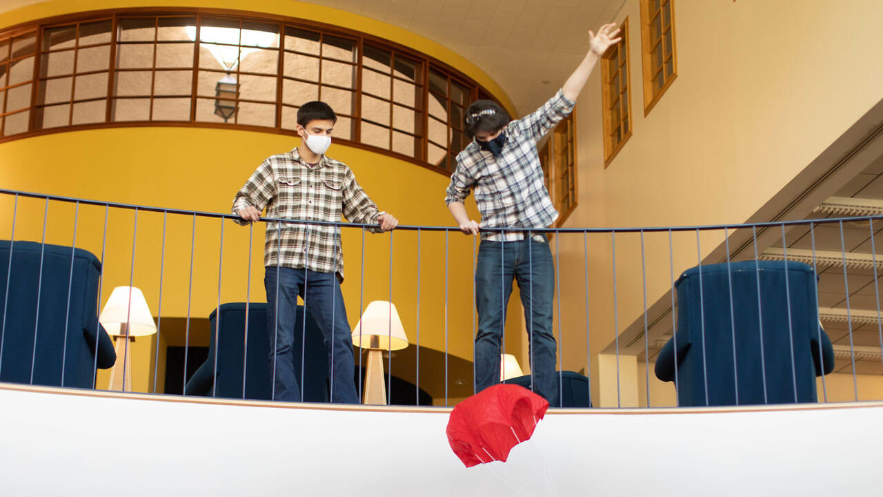 Two students stand at a banister while watching a parachute fly down.