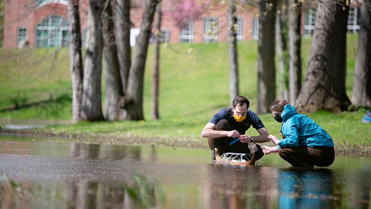 A student and professor kneeling down near a pond testing the wooden row boat.