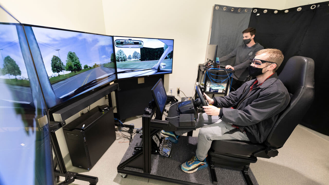 A student sitting in a chair holding a steering wheel using a driving simulator looking at three large screens.