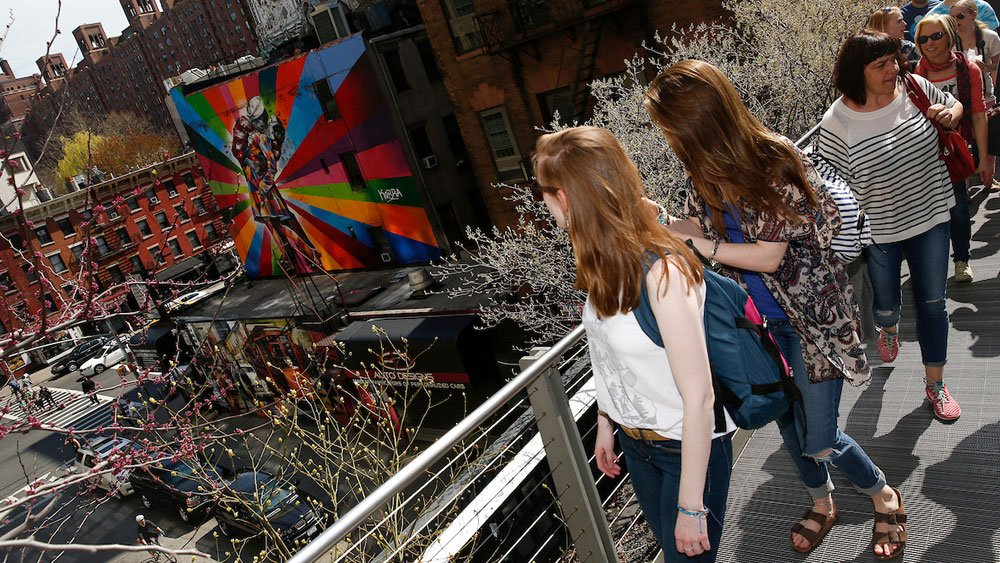 Two students look down from the High Line in New York City at the street below and a colorful mural.