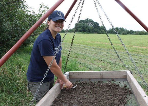 Erika Danella stands in a field working with a screen and trowel searching through dirt.