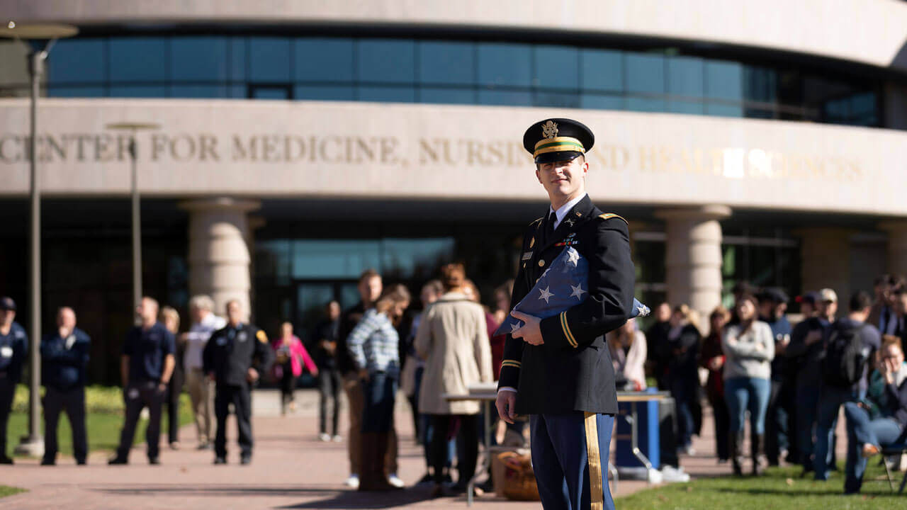 Veteran in front of crowd at center of medicine