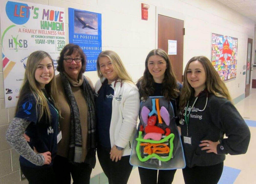 Four female nursing students stand with their female professor.