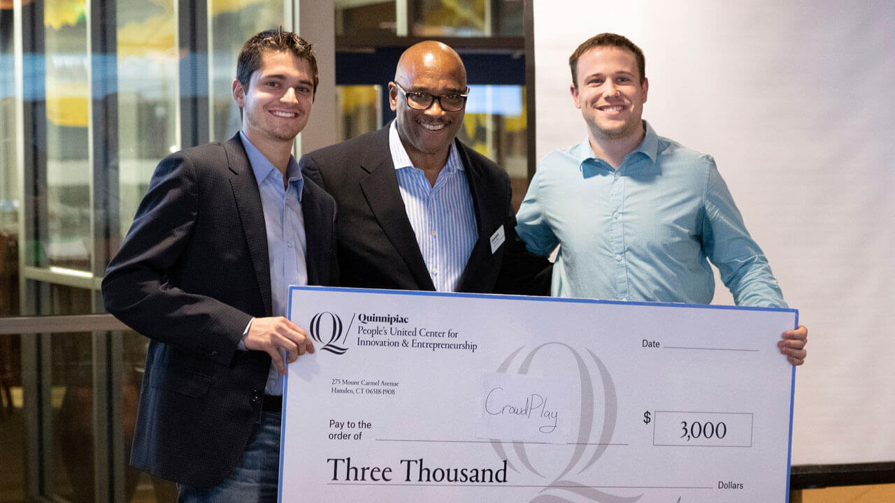 Andrew Pizzi '19, left, and alumni Mike Cusano, right, accept a $3,000 check from Fred McKinney, director of the People's United Center for Innovation & Entrepreneurship at Quinnipiac.