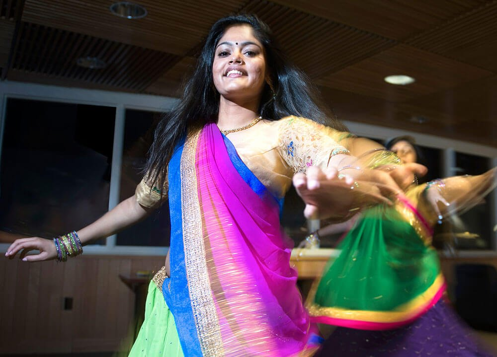 A student performs a Bollywood dance wearing a colorful gown