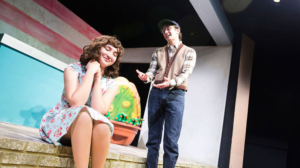 Two students act out a scene in a play in which a male character pleads with a female character