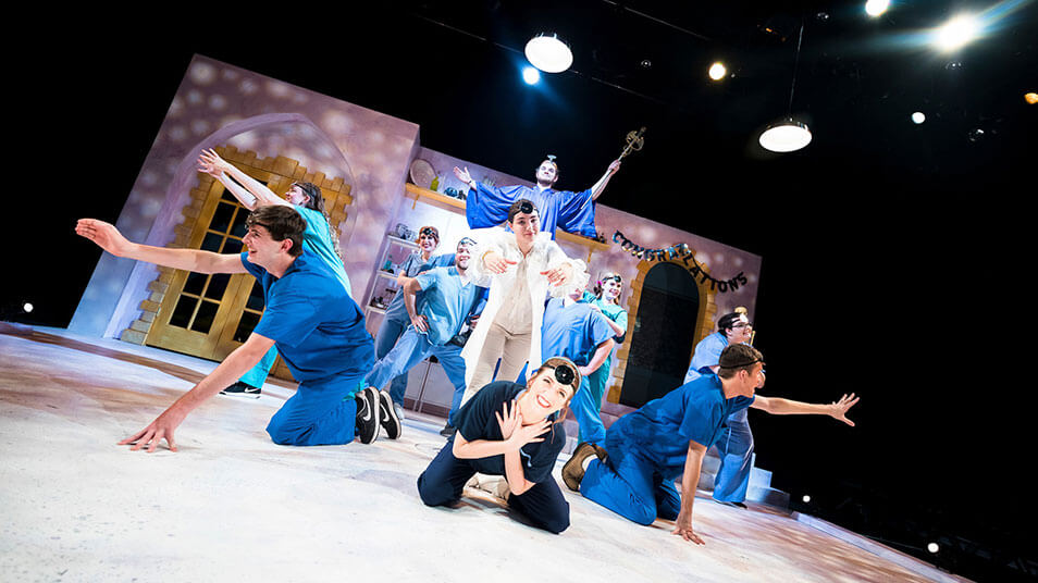 A group of students act out a scene in which one character dressed in all white is surrounded by blue costumed actors