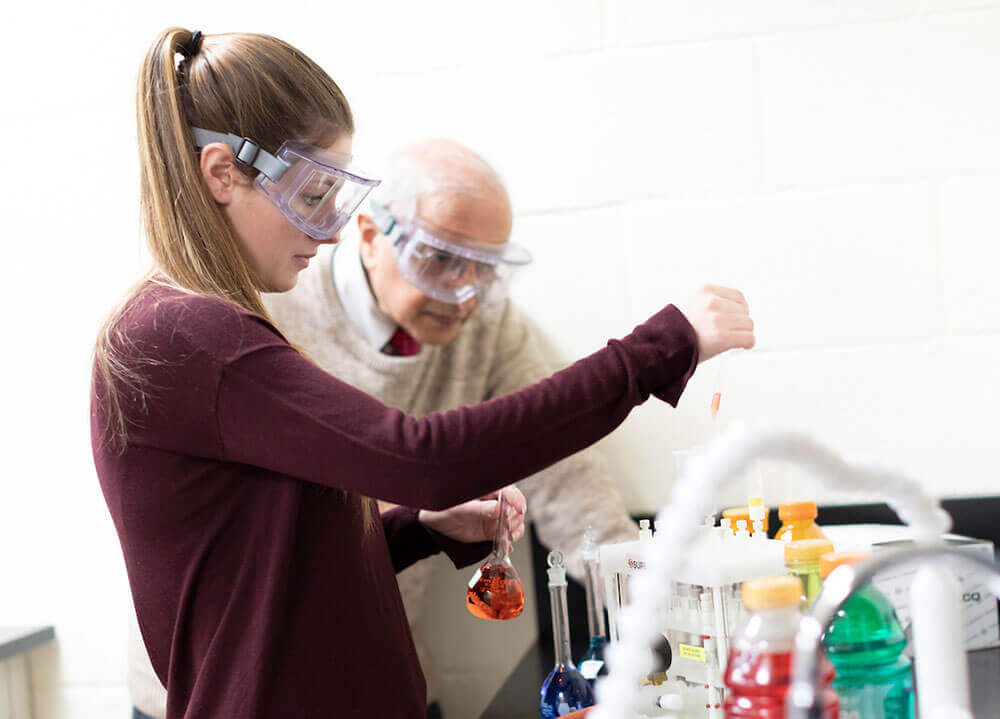 A student carefully uses a dropper and beaker to conduct a lab experiment while a chemistry professor watches on