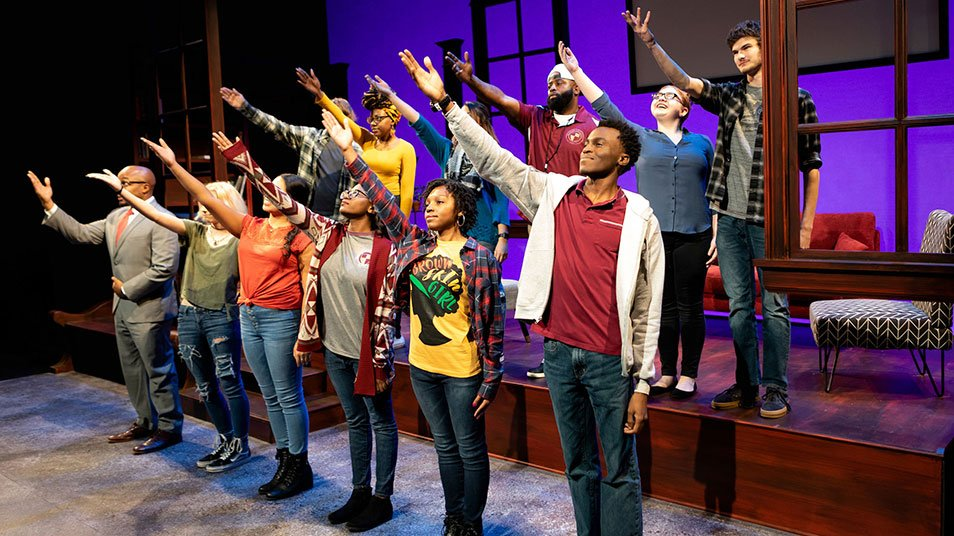 A large cast of students sing a song and reach their hands to the sky during a theater scene