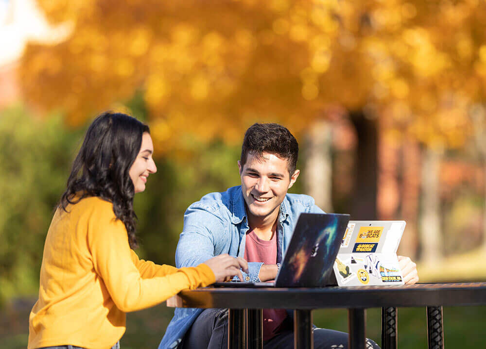 Two students sit at an outdoor table with their laptops with yellow fall foliage in the background
