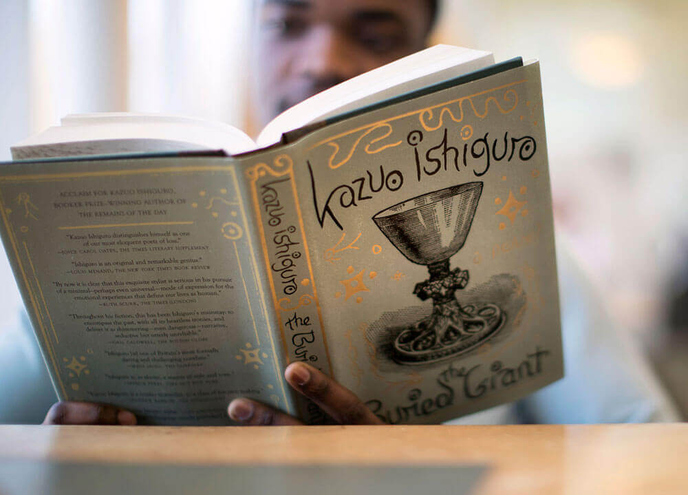 A closeup shot of an English student reading a hardcover book by Kazuo Ishiguro
