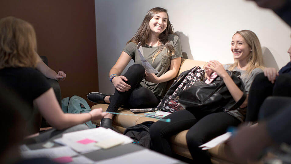 Students smile and lounge on a couch while being interviewed for a theater audition