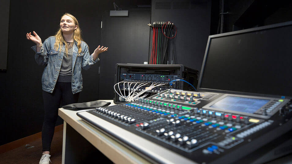 A student gives a tour of the control room of the QU Theatre Arts Center