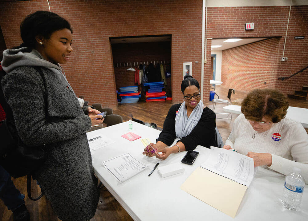 A political science student waits to cast her vote in an election at the Hamden public library