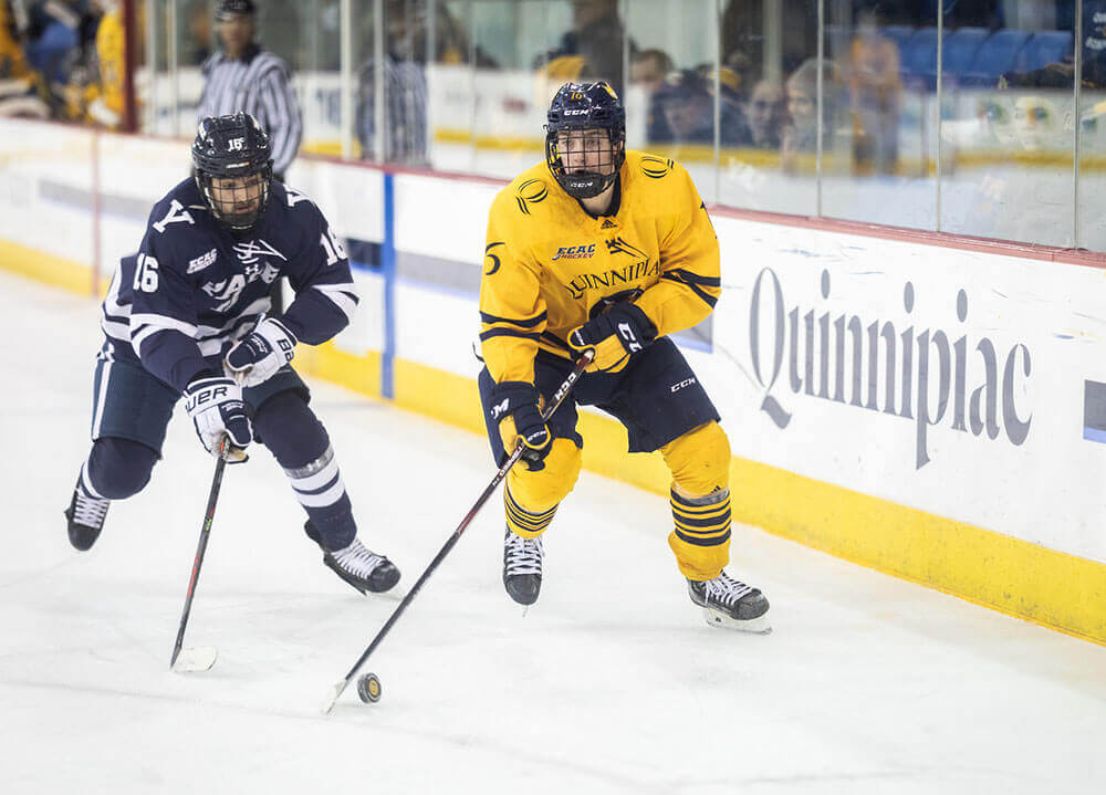 A Quinnipiac men's hockey player skates with the puck on home ice