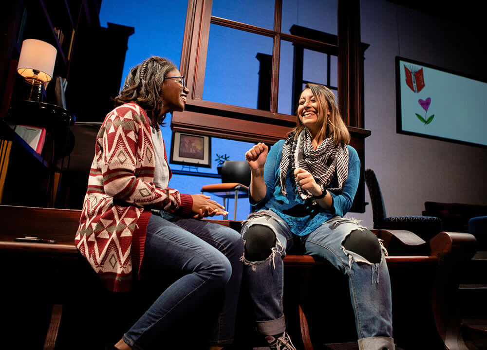 "Two female theater students smile and act out a scene from the production of ""Baltimore"""