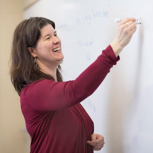Professor Catherine Solomon writes on a white board