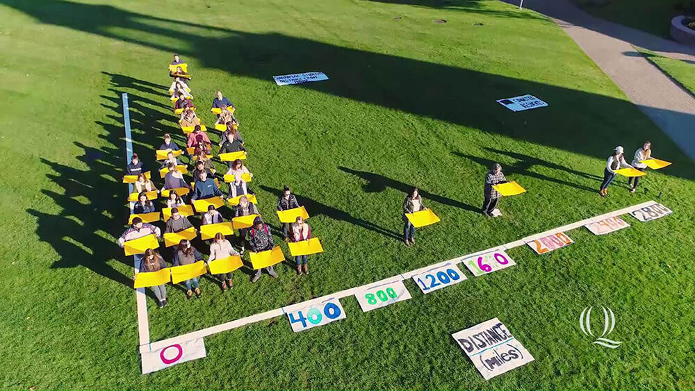 Aerial view of students forming a bar graph, starts video