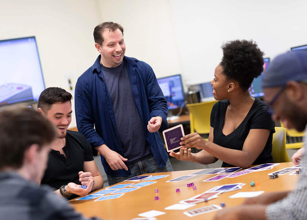 A group of game design and development students laugh as they play a card and dice game during a classroom exercise