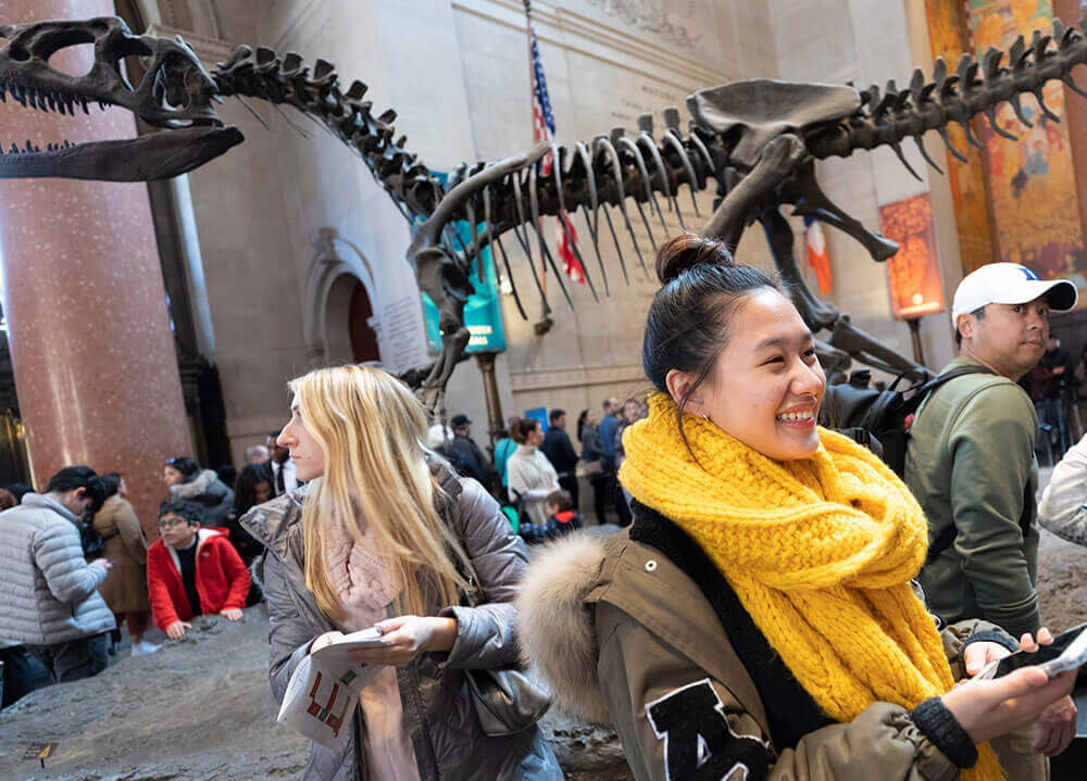 Quinnipiac students smile and stand in the Natural History museum in New York City with a T-rex skeleton in the background