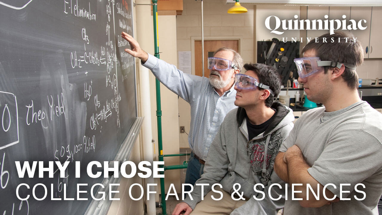 Two arts and sciences students and their professor read equations on a chalkboard