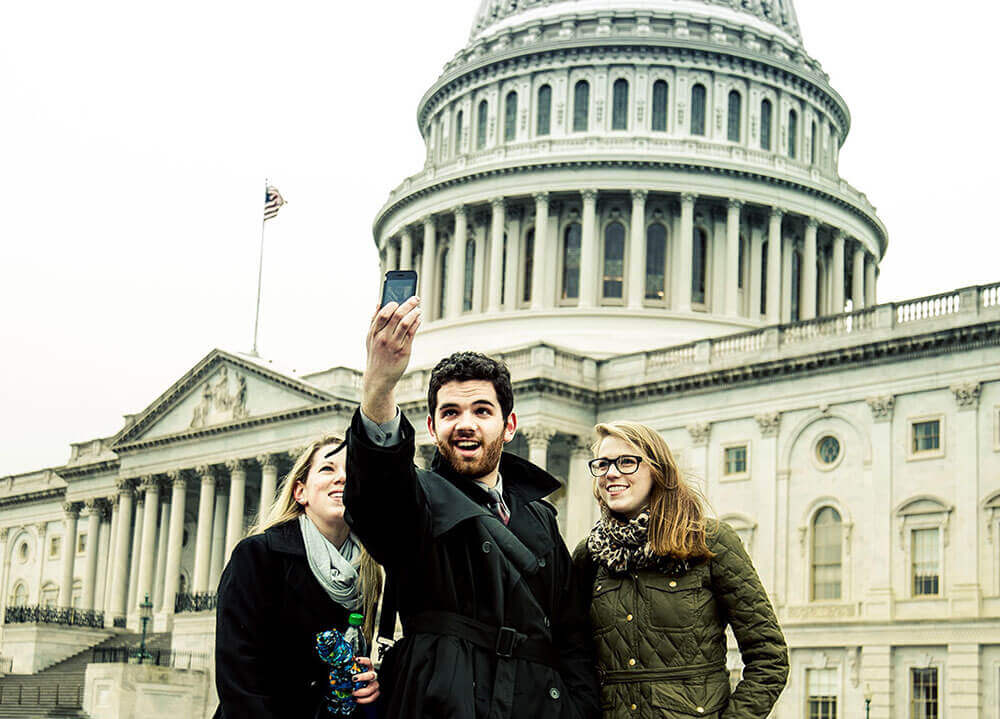 Three students take a selfie in front of the Capitol building in Washington, D.C.