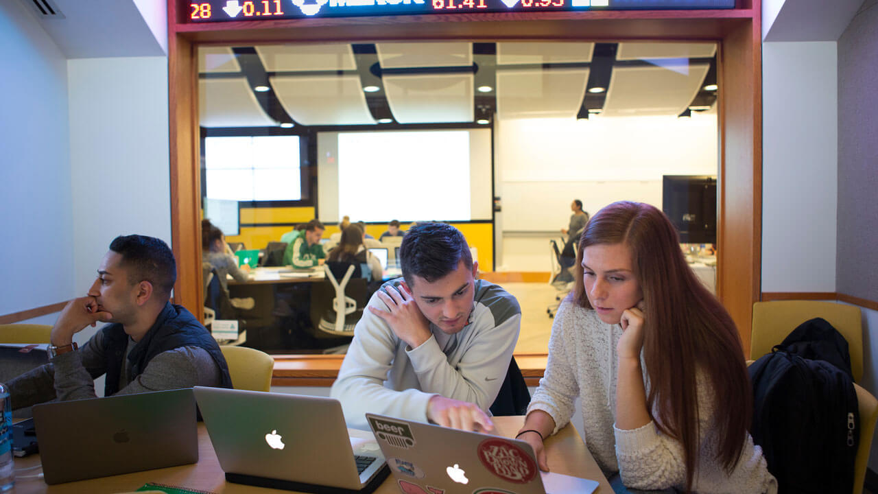 Students work on their laptops in the study room outside the Financial Technology Center.