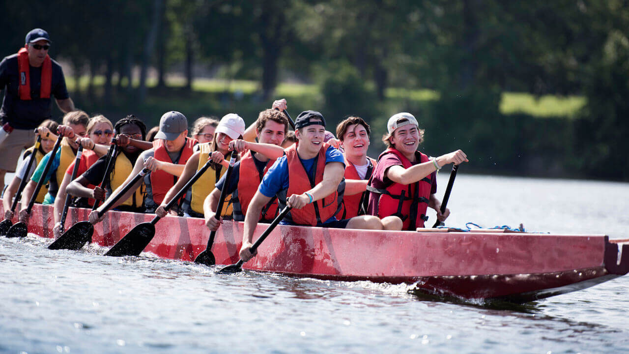 Students row a dragon boat during a team building event