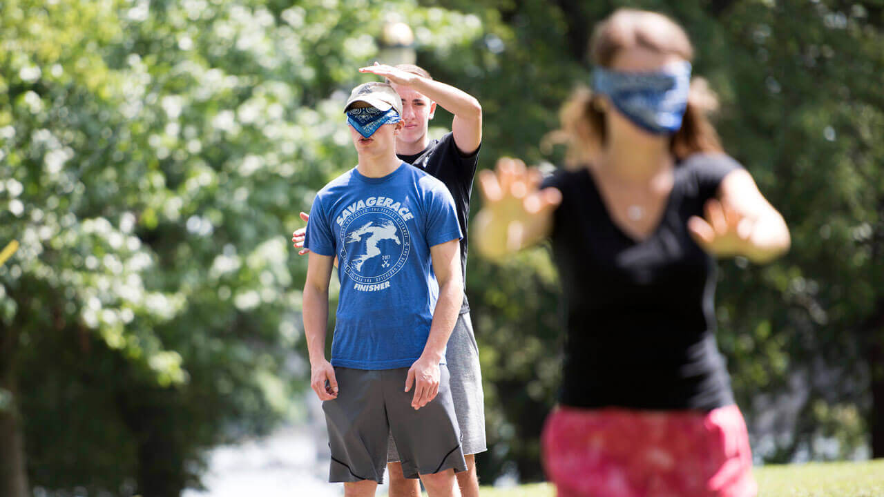 A students standing in a field blindfolded.